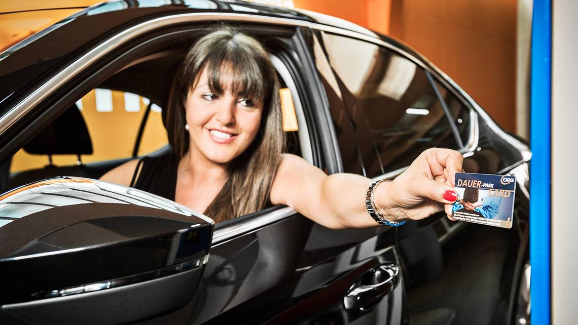 Eine Dame parkt mit der OPG Dauer-ParkCard in einem OPG-Parkhaus ihrer Wahl.
